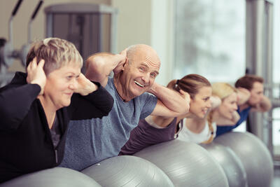 Elderly couple doing pilates class at the gym with a group of diverse younger people balancing on the gym ball with raised arms to tone their muscles in an active retirement concept-1