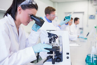 Side view of busy group of researchers working on experiments in the laboratory