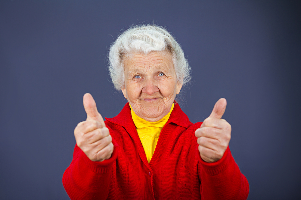 Closeup portrait senior, mature, happy, smiling excited natural woman giving thumbs up sign with fingers, isolated blue background. Positive emotions, facial expressions, symbols, feelings, attitude