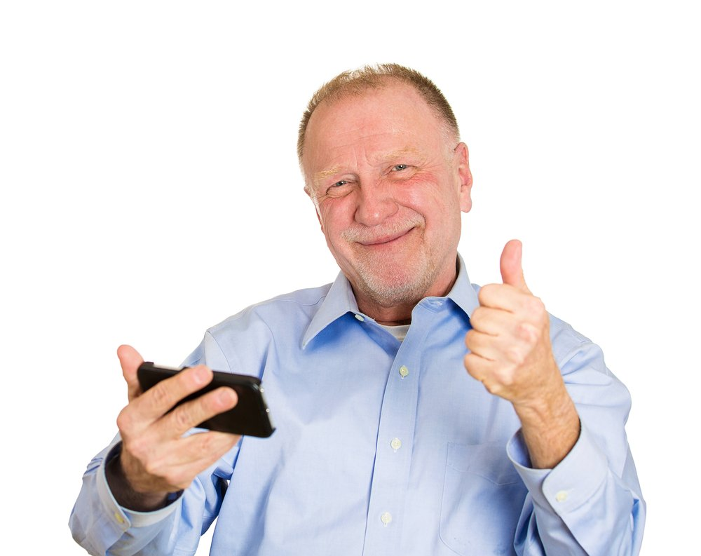 Closeup portrait, senior man, looking happy, excited at something on a cell phone, watching sports game match or reading an sms, e-mail, viewing latest news, isolated white background.