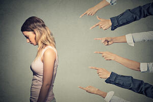 Concept of accusation guilty person girl. Side profile sad upset woman looking down many fingers pointing at her back isolated on grey office wall background. Human face expression emotion feeling