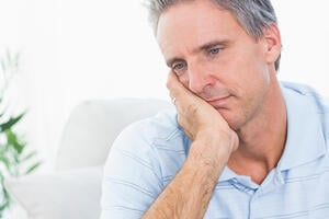 Depressed man thinking at home on couch