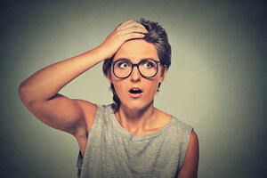 Surprise astonished woman. Closeup portrait woman with glasses looking surprised in full disbelief wide open mouth isolated grey wall background. Human emotion facial expression body language.