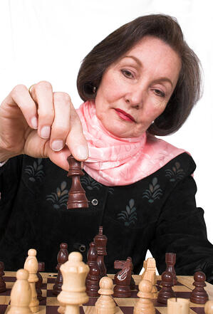 business woman playing chess over a white background